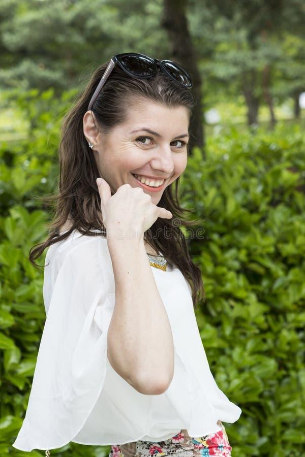 La giovane rappresentazione castana sorridente mi chiama gesto fotografia stock