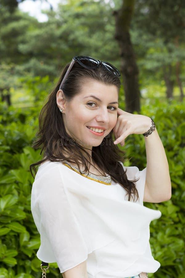 La giovane rappresentazione castana sorridente mi chiama gesto fotografie stock