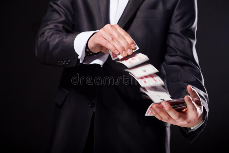 La giovane rappresentazione del mago inganna usando le carte dalla piattaforma Fine in su fotografia stock libera da diritti