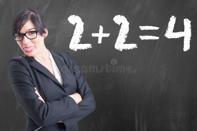 La giovane scrittura dell'insegnante per la matematica numera sulla lavagna fotografia stock libera da diritti