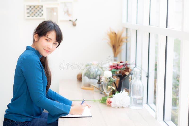 La giovane scrittura dello scrittore della donna dell'Asia del bello ritratto sul taccuino o sul diario con felice, stile di vita immagine stock