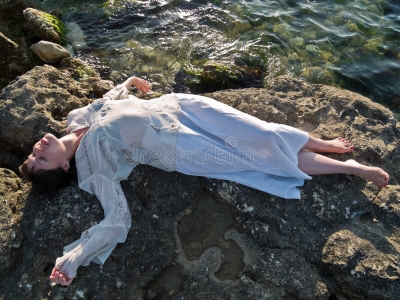 La giovane signora l'etica veste la menzogne sulla roccia del mare fotografie stock libere da diritti