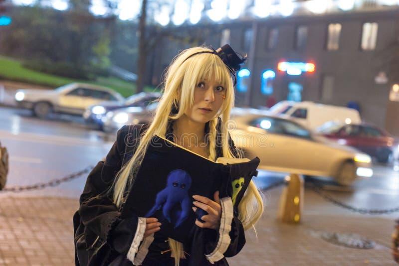La giovane signora si è vestita in costume nero, avendo libro in mani immagine stock