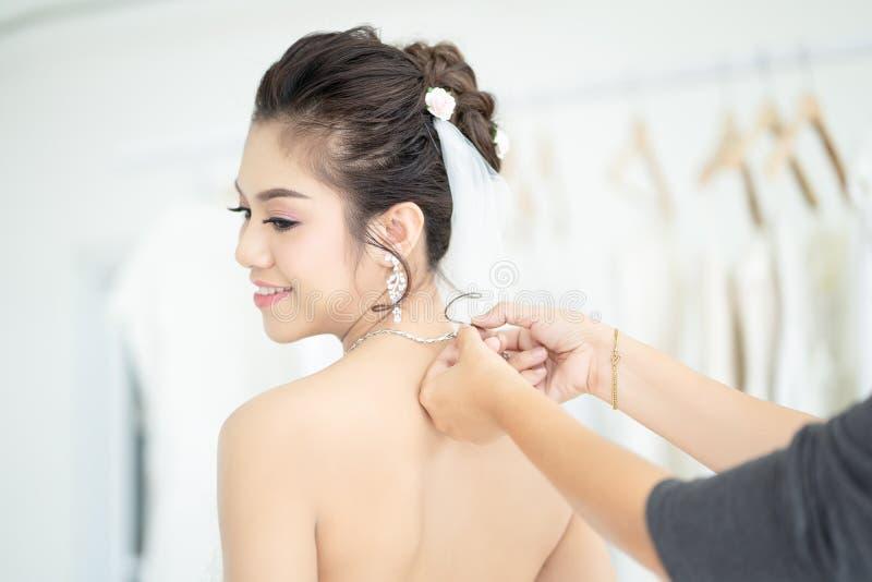 La giovane sposa asiatica attraente sta provando sulla collana dei gioielli con l'assistente di nozze nel salone moderno di nozze fotografie stock libere da diritti