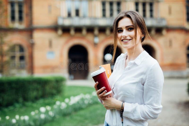 La giovane studentessa di talento si è vestita in abbigliamento casuale che cammina intorno alla città Donna castana attraente ch immagine stock libera da diritti