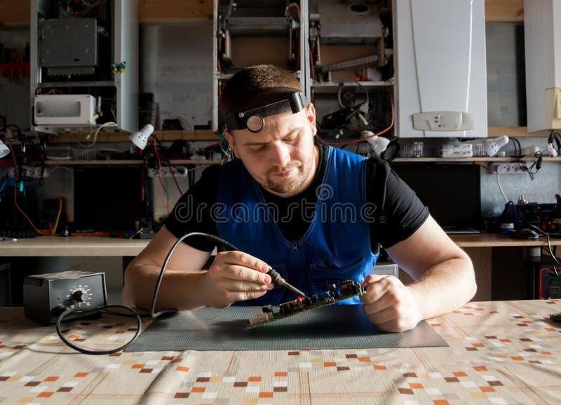 La giovane tecnologia maschio energetica o l'ingegnere ripara l'attrezzatura elettronica fotografia stock