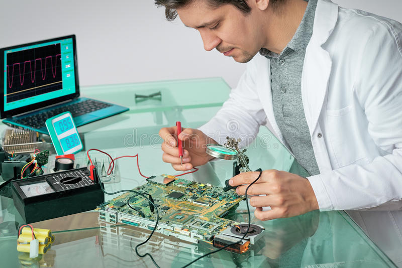 La giovane tecnologia maschio energetica ripara l'apparecchio elettronico immagine stock