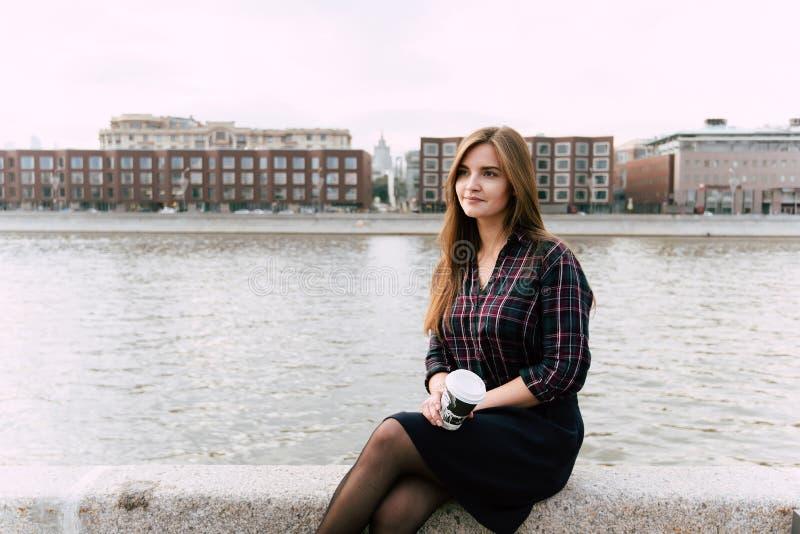 La giovane tenuta alla moda della ragazza dei pantaloni a vita bassa porta via la tazza di caffè mentre sedendosi sul pilastro de fotografia stock