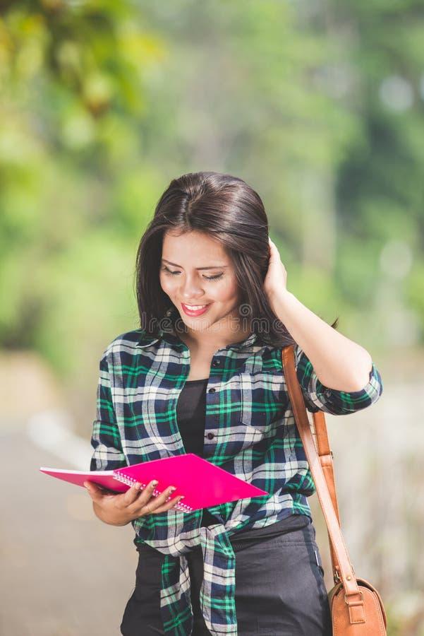 La giovane tenuta asiatica della studentessa prenota mentre cammina sul PA fotografia stock