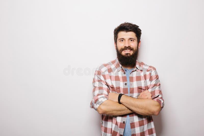 La giovane tenuta barbuta bella dell'uomo ha attraversato le mani e l'esame della macchina fotografica immagine stock