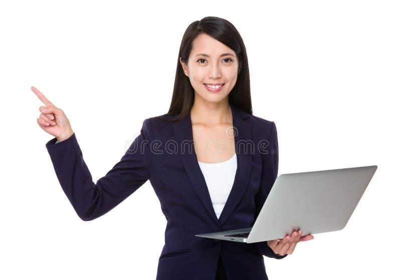 La giovane tenuta della donna di affari con il computer portatile ed il dito indicano la u fotografia stock
