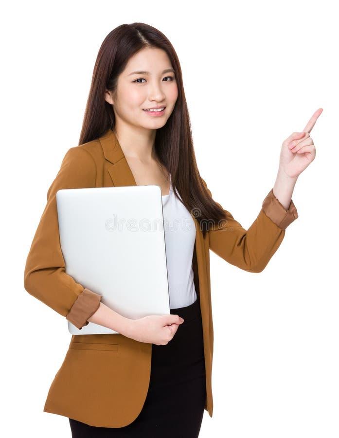 La giovane tenuta della donna di affari con il computer portatile ed il dito indicano la u immagine stock