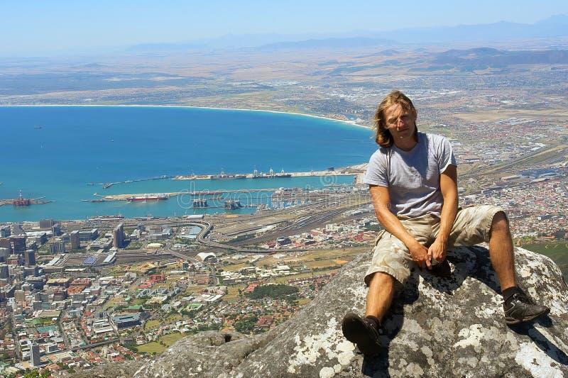 La giovane viandante si siede sulla roccia fotografia stock libera da diritti
