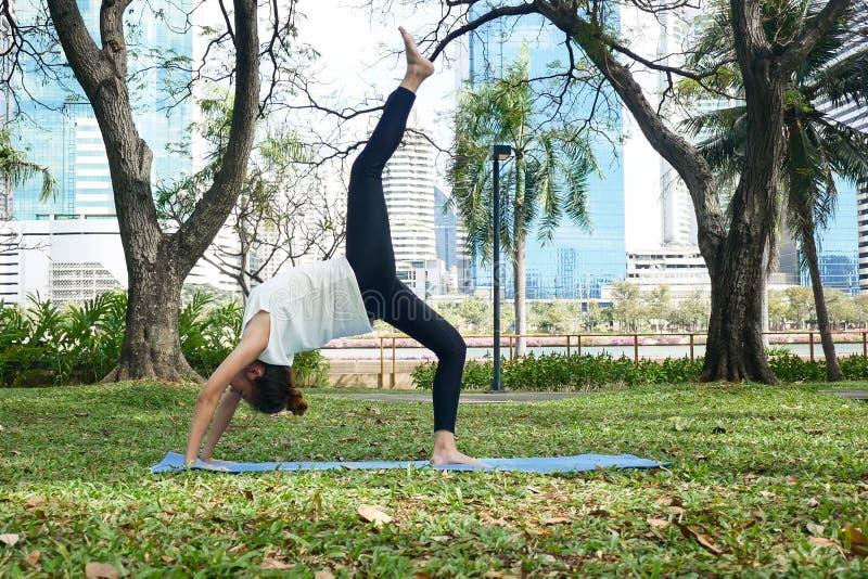 La giovane yoga asiatica della donna all'aperto tiene la calma e medita mentre pratica l'yoga per esplorare la pace interna immagini stock