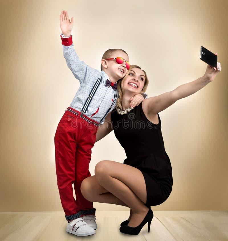 La giovani madre e figlio sono fotografati su un telefono cellulare, facente il selfie Alla moda, d'avanguardia, moderno fotografie stock