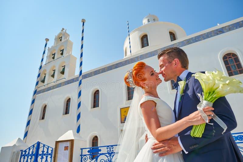 La giovani sposa e sposo delle coppie celebrano le nozze su Santorini fotografia stock libera da diritti