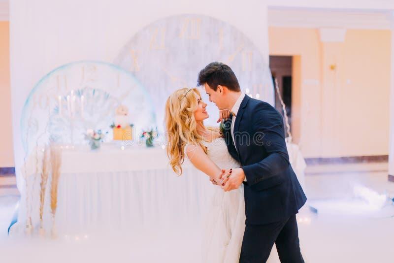 La giovani sposa e sposo felici ballano nel corridoio di nozze immagine stock libera da diritti