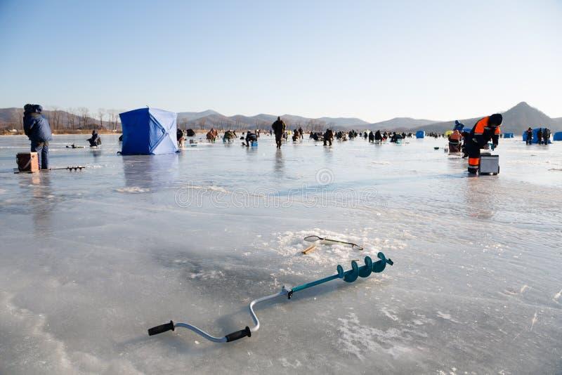 La glace de pêcheur visse dans le premier plan, pêchant en Russie image stock