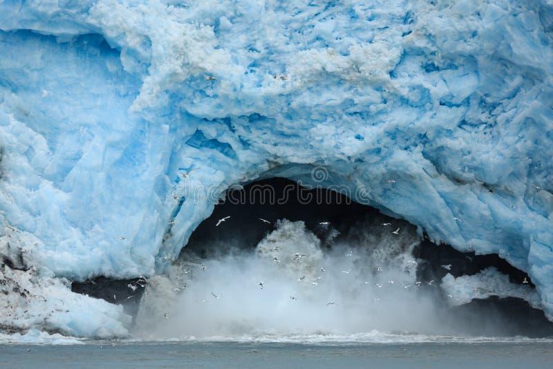 La glace de spéléologie du glacier bleu lumineux éclabousse dans l'eau quand elle tombe photo stock