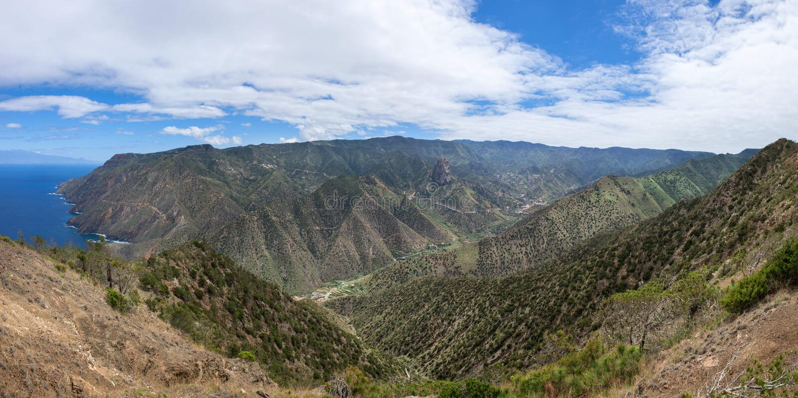 La Gomera - Valley of Vallehermoso with the north coast. Panorama over the valley of Vallehermoso with the central Roque El Cano to the north coast. At the back stock photos