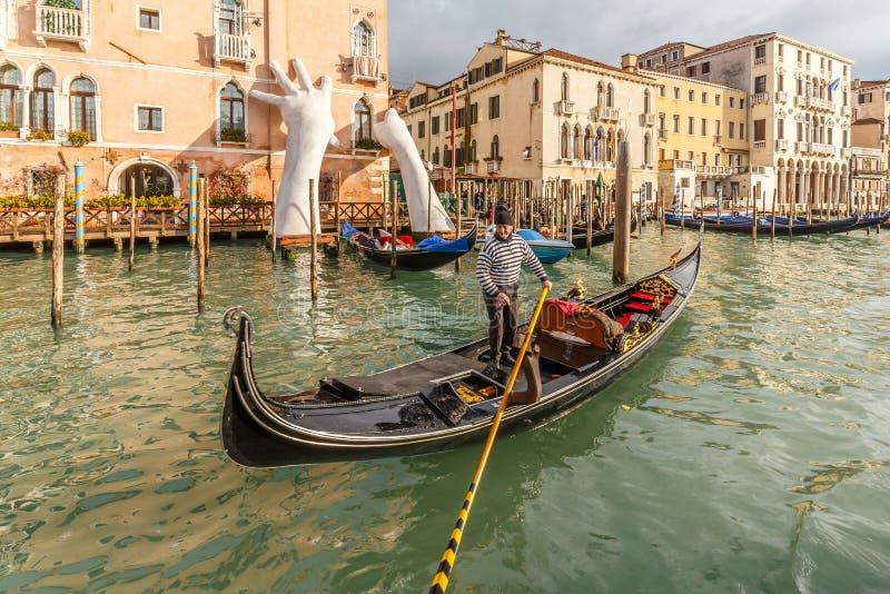 La gondolière pagaie au-delà de la sculpture des mains géantes à Grand Canal à Venise images stock