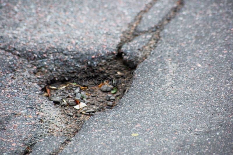 La gouge sur l'asphalte est étroite photo stock