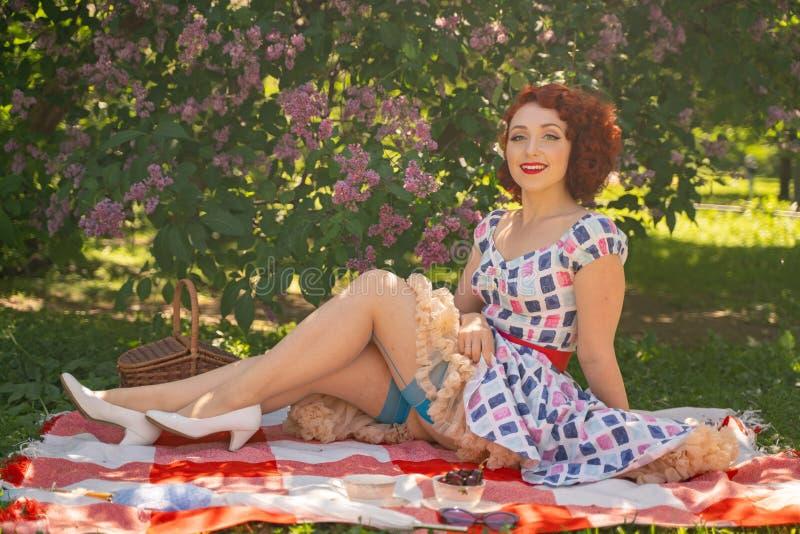 La goupille heureuse rousse vers le haut de la fille dans la robe d'été de cru et des bas classiques avec une couture dans le dos photographie stock