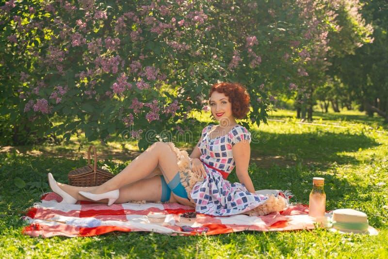 La goupille heureuse rousse vers le haut de la fille dans la robe d'été de cru et des bas classiques avec une couture dans le dos photographie stock libre de droits