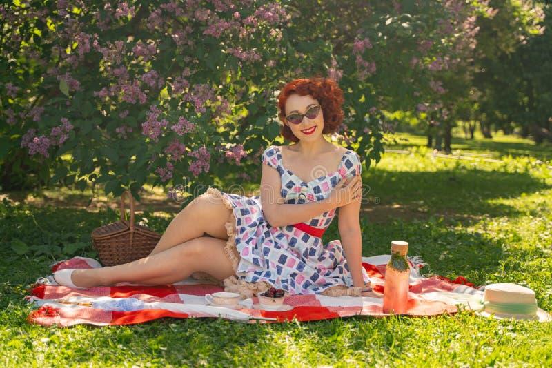 La goupille heureuse rousse vers le haut de la fille dans la robe d'été de cru et des bas classiques avec une couture dans le dos photo stock