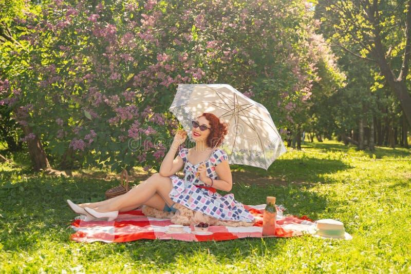 La goupille heureuse rousse vers le haut de la fille dans la robe d'été de cru et des bas classiques avec une couture dans le dos images libres de droits