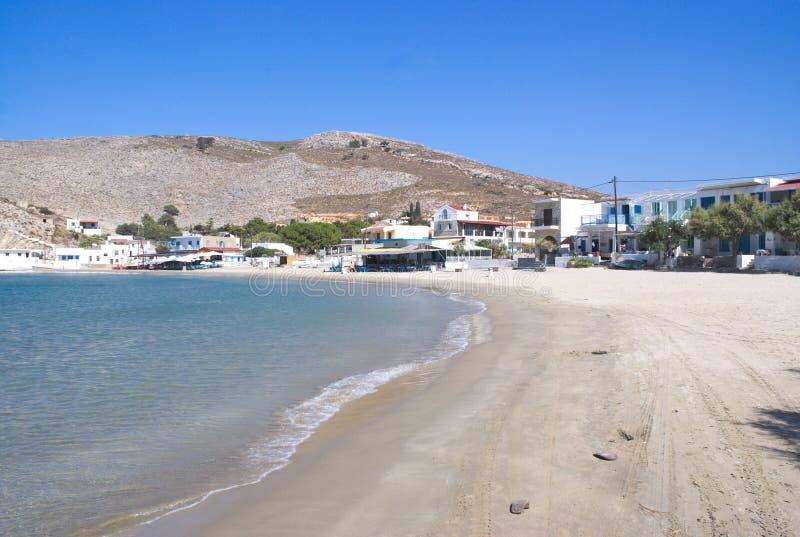 La Grèce, l'île de Pserimos dans le Dodecanese La plage de port chez Avalakia, avant les bateaux de voyage de jour arrivent images libres de droits