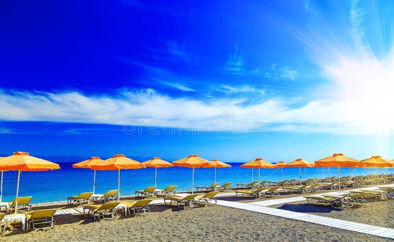 La Grèce, les parapluies tubulaires et les lits pliants jaunes sur le Pebble Beach à la mer Égée de Rhodes, Grèce photographie stock libre de droits