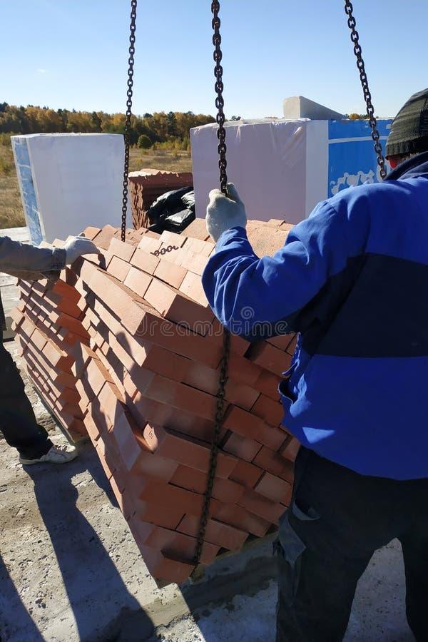 la grúa suministra los materiales de construcción al edificio del cielo azul del otoño imagen de archivo libre de regalías