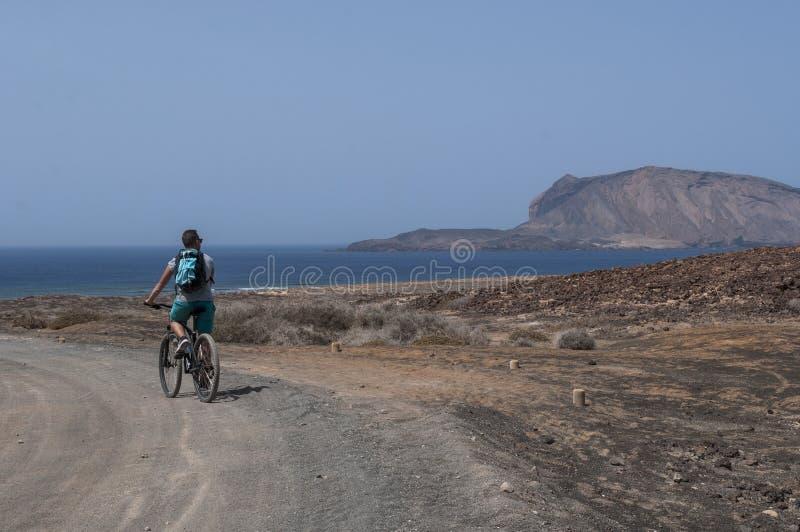 La Graciosa, Fahrrad, fahrend, Radfahrer, Wüste rad, vulkanisch, Landschaft, Schotterweg, weg von der Straße und erforschen, Lanz lizenzfreies stockbild