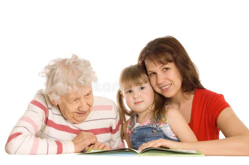 La grand-mère avec la petite-fille a affiché le livre photographie stock libre de droits