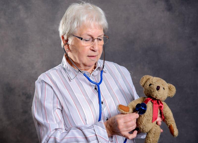 La grand-mère avec le stéthoscope est docteur de marionnette pour l'ours de nounours photos stock