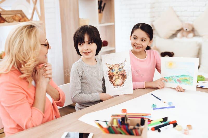 La grand-mère avec plaisir regarde des dessins des petits-enfants Le petit garçon a dessiné le hibou sur la feuille Paysage peint photographie stock