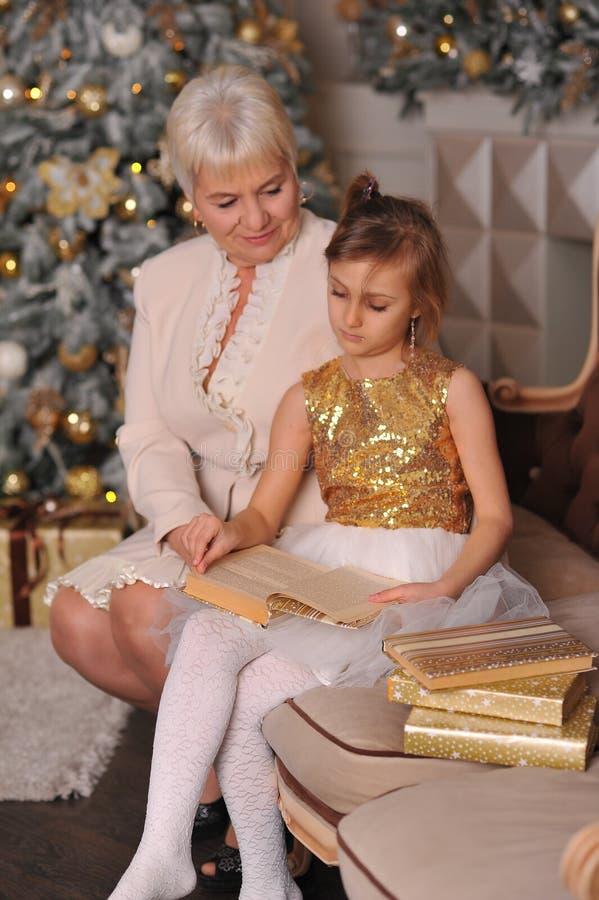 La grand-mère avec sa petite-fille lisent près du Christma photo libre de droits