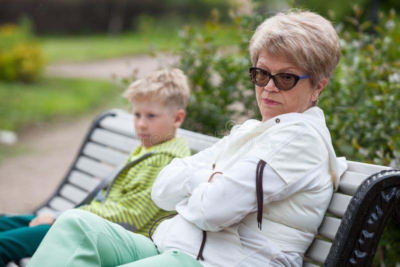 La grand-mère et le petit-fils européens sont en conflit, deux personnes se reposent dans des poses fermées sur le banc en parc image stock