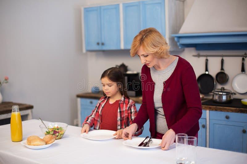 La grand-mère et la petite-fille étendent la table image libre de droits