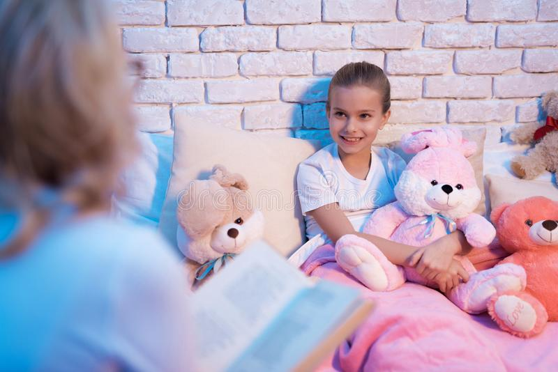 La grand-mère et la petite-fille lisent des contes de fées réservent la nuit à la maison photographie stock libre de droits