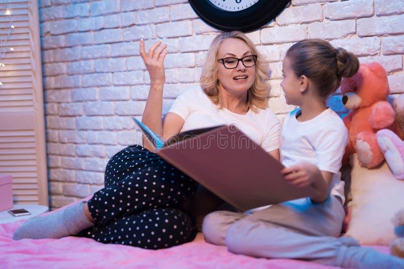 La grand-mère et la petite-fille lisent le livre de lange la nuit à la maison photos stock