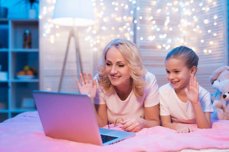 La grand-mère et la petite-fille parlent avec la famille sur l'ordinateur portable la nuit à la maison photos libres de droits