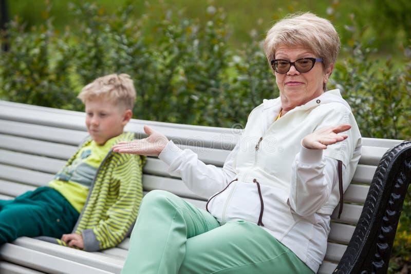 La grand-mère lui donne des mains après conversation désagréable à son petit-fils, deux personnes photographie stock libre de droits