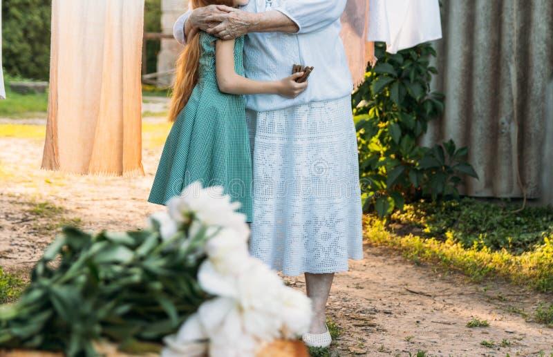 La grand-mère, une femme agée dans le blanc, supports de vêtements de vintage et étreint sa petite-fille, une fille dans une robe images libres de droits