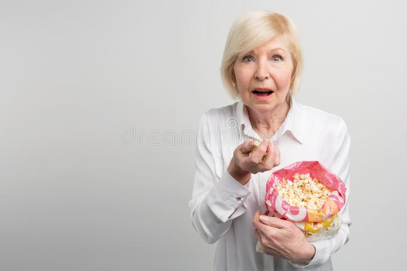 La grand-maman aime observer des bandes dessinées, des films et la série télévisée différente - Al qui les jeunes ainsi comme pou photo stock