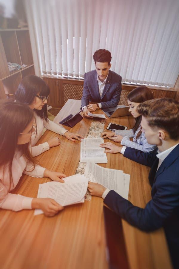 La grande équipe de personnes travaille à une table pour les ordinateurs portables, comprimés et papiers, sur le fond un grand image libre de droits