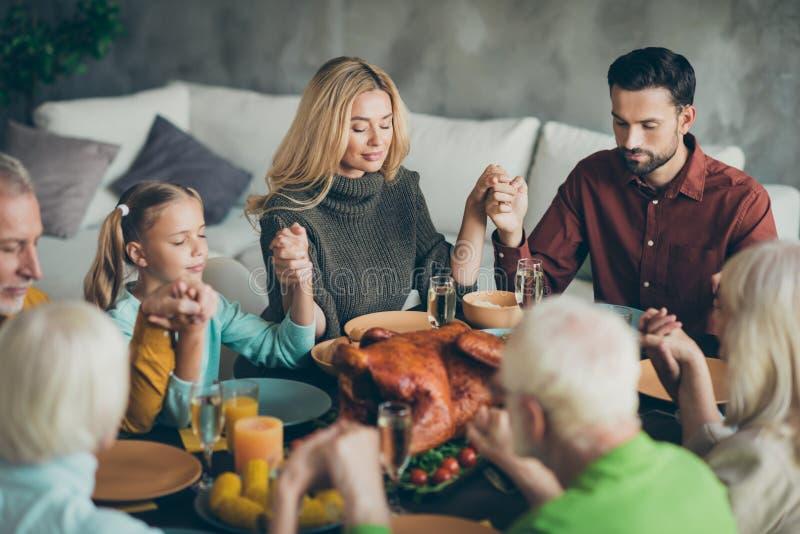 La grande assemblea familiare il giorno del Ringraziamento si siede a tavola il pranzo di ottobre tenuto per mano pregando i pare immagine stock libera da diritti