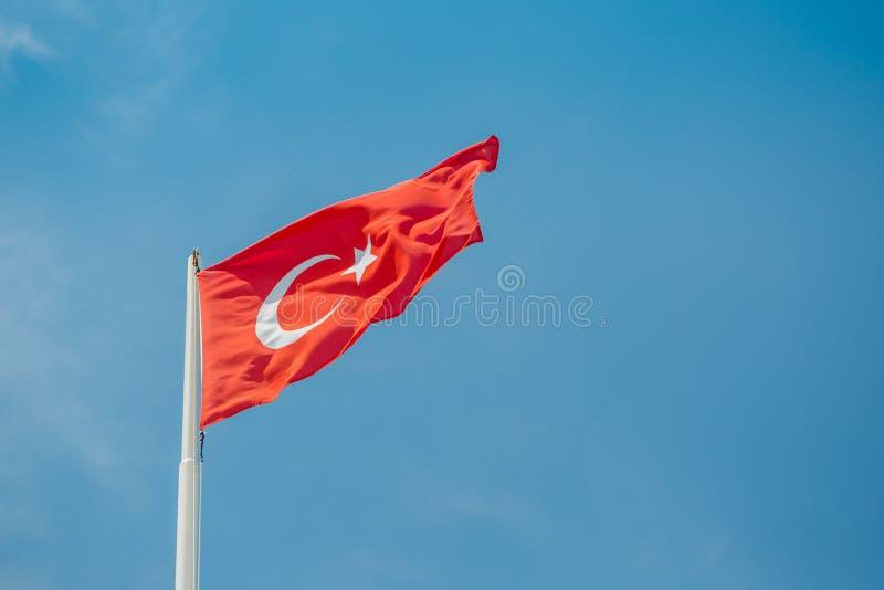 La grande bandiera della Turchia sta ondeggiando nel vento contro il cielo blu sulla costa del mar Mediterraneo immagine stock