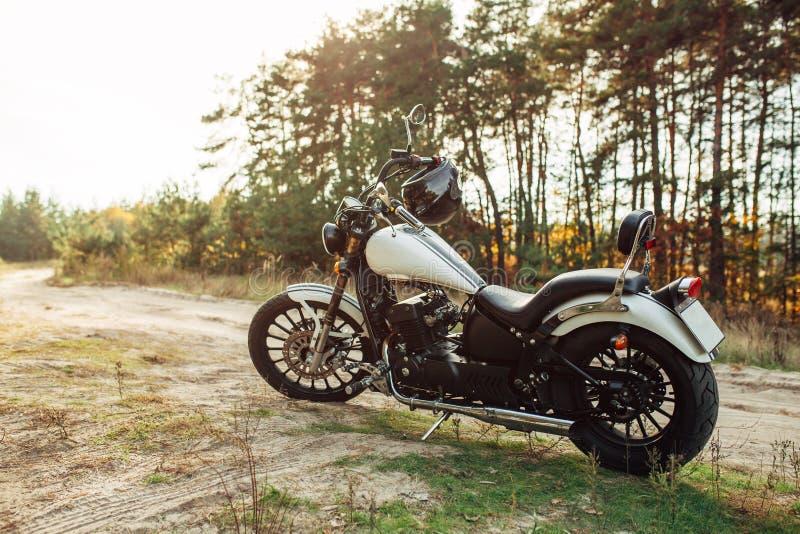 La grande bici fresca sta su una strada campestre sabbiosa contro lo sfondo di un'abetaia e di bello tramonto fotografia stock